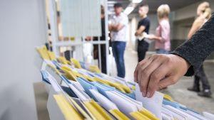 henkilö ottamassa äänestyslippua