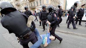 Kaksi musta-asuista mellakkapoliisia kypärät päässään kantaa mielenosoittajaa pietarilaisella kadulla. Toinen poliisi pitää miestä jalasta, toinen kädestä. Mies roikkuu heidän välissään. Taustalla toiseen suuntaan kävelee muita poliiseja.
