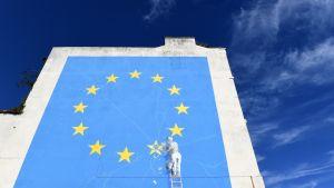 Britannian Doveriin ilmestynyt katutaiteilija Banksyn seinämaalaus, jossa rakennustyöläinen poistaa yhtä tähteä EU:n lipusta.