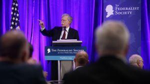 Yhdysvaltain kansallisen turvallisuuden neuvonantaja John Bolton pitää puhetta, lavalla myös Yhdysvaltojen lippu, etualalla yleisöä