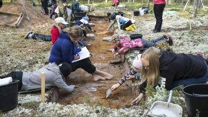 Koululaisia tekemässä arkeologisia kaivauksia.