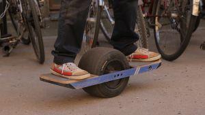 Yksipyöräinen tasapainolauta Onewheel, jonka päällä mies polvista alaspäin. Taustalla pysäköityjä polkupyöriä Kaapelitehtaan pihalla.