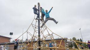 Oppilaat ovat kiiveneet koulun  pihalla olevan kiipeilytornin huipulle.