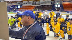Jääkiekkojoukkue Jukureiden pelaajat seuraavat, kun päävalmentaja Pekka Kangasalusta piirtää fläppitauluun jääkiekkokaukalossa.