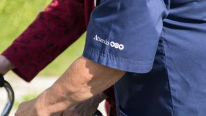 Attendon lähihoitaja ulkoiluttaa Hopehelmen asiakasta