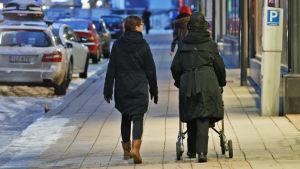 Nuori ja vanha nainen kävelevät kadulla.