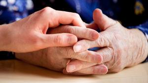 Vanhemman ja nuoremman ihmisen kädet.