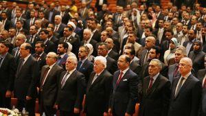 Pääosin miehiä seisomassa puvut yllään.