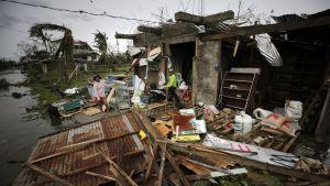 Hajonnut rakennus, seinä kaatunut betonipalkeista töröttää metallia. Kaksi ihmistä seisoo edustalla.