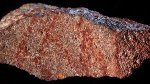 Kivi, jossa on ristikkäin punaisia viivoja.
