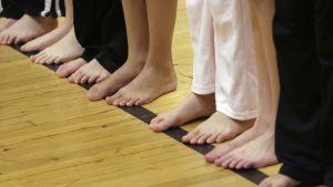 Viidesluokkalaisia liikuntatunnilla rivissä.