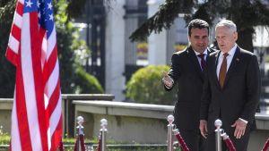 Kuvan oikeassa laidassa Makedonian pääministeri Zoran Zaev ohjaa Yhdysvaltain puolustusministeriä Jim Mattisia eteenpäin kohti köysillä rajattua käytävää, vasemmalla Yhdysvaltain lippu.