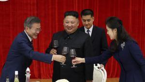 Moon Jae-in ja Kim Jong-un kilistelevät hymyillen