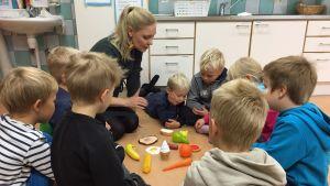 Lapsia piirissä lattialla opetushetkessä, keskellä muovisia ruokatarpeita