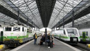Junat seisovat raitella ja matkustajat asemalaiturilla Helsingin päärautatieasemalla.