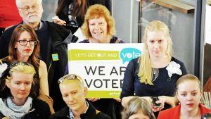 Naisia äänestyskampanjakyltin kanssa.