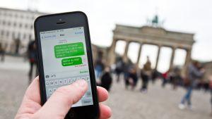 Ihminen pitää kännykkää kädessään niin, että ruudulla näkyy viestejä, taustalla Brandenburgin portti.