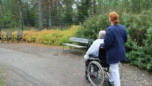 Hoivakodin asukas ulkoilee pyörätuolissa.