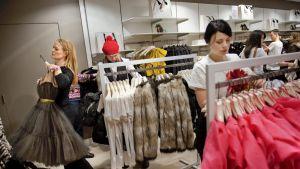Nuoria naisia vaatekaupassa.