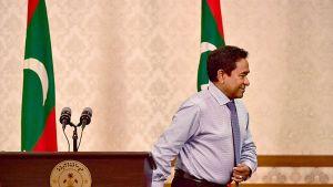 Malediivien vaalit hävinnyt presidentti Abdulla Yameen kävelee pois puhujapöntästä.