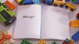 """Lasten lelujen ympäröimän päiväkirjan sivulla lukee """"mitkä treffit?"""""""