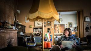 Helena Lehmus istuu nojatuolissa, katsoo vanhaa kakluunia ja selailee papereita.
