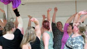 Naisia käsi ylhäällä ryhmässä tanssitunnilla