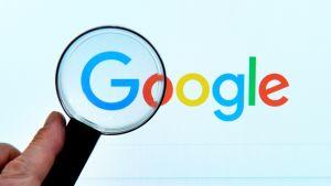 Google haku  tietokoneen ruudulla ja suurennuslasi.