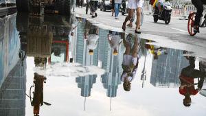 Kiinalaiset työläiset ja jalankulkijat heijastuvat vesilätäköstä.