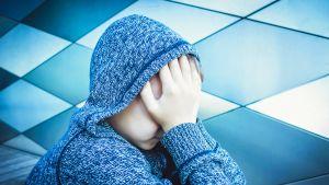 Nuori poika istuu lattialla kädet kasvoilla.