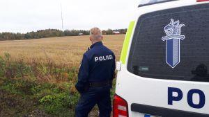 Poliisiauto ja poliisi viljapellon laidalla.