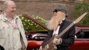 Soitinrakentaja Kari Nieminen ja kitaristi Billy Gibbons. Gibbonsilla kädessä Versoul Raya Blue Light. Taustalla Johan Erikssonin Dodge Charger vm. 1968.