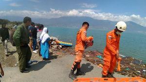 Pelastushenkilökuntaa rannalla etsimässä uhreja.