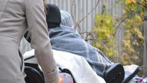 Nainen työntää vanhusta pyörätuolissa.