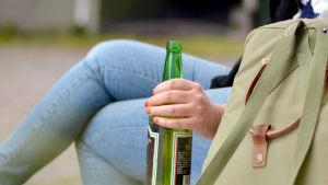 Nuori nainen istuu penkillä pullo kädessään.