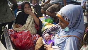 Nainen piti sylissään vastasyntynyttä lapsenlastaan Palussa, Indonesiassa 2. lokakuuta.