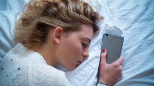 nainen nukkuu älypuhelimen vieressä