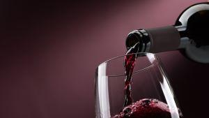 Viinipullosta kaadetaan viiniä lasiin.