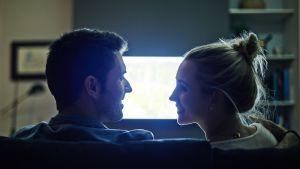 Mies ja nainen katsoo toisiaan sohvalla, telkkarista loistaa valo heidän kasvoilleen.