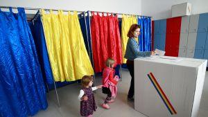 Nainen äänestää, mukana myös kaksi lasta.
