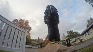 Erityislapsi Eevertti odottelee koulutaksia ison kiven päällä.