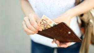 nainen ottaa seteliä lompakosta