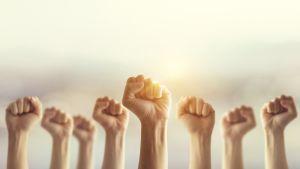 Naisten käsiä ylhäällä nyrkissä auringonsäteen osuessa yhteen käteen.