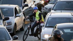 Pyöräilijä yrittää löytää tiensä liikenneruuhkassa autojen keskellä Pariisissa.