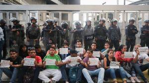 Ihmisiä istuu katukivetyksellä lappu käsissään, heidän takanaan seisoo miehiä aseistettuina kypärät päässään.