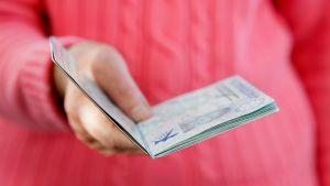nainen ojentaa passia