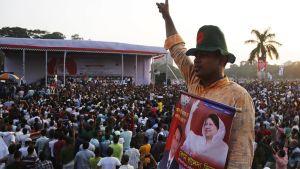 Suuri määrä ihmisiä on kentällä puhujalavan edessä. Etualalla seisoo hattupäinen mies kyltti kaulassaan. Kyltissä on ainakin entisen pääministerin Khaleda Zian kuva.
