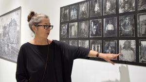 Taiteilija tarkastelee työtään, joka esittelee vanhoja mustavalkoisia valokuvia