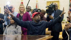 Mies punainen lippalakki päässä kädet levällään, taustalla miehiä kameroiden kanssa.