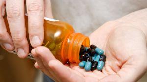 Mies valuuttaa mustasinisiä pillereitä lääkepurkista kämmenelle.